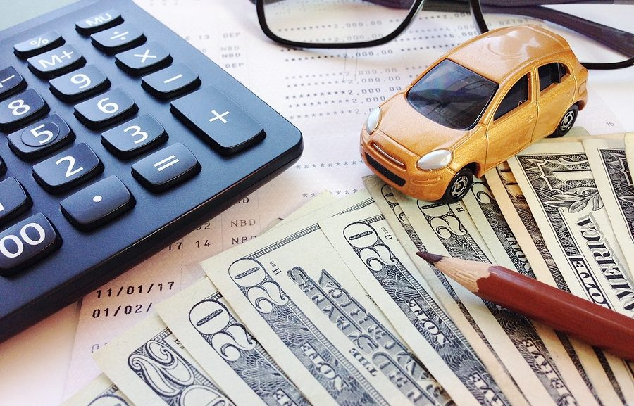 Los Angeles car dealership no credit - Business, finance, savings, banking or car loan concept : Miniature car model, pencil, money, calculator, eyeglasses and savings account passbook or financial stateme